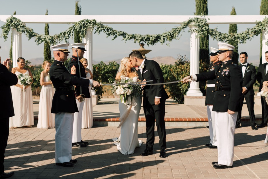 first kiss as a married couple under a sword arch