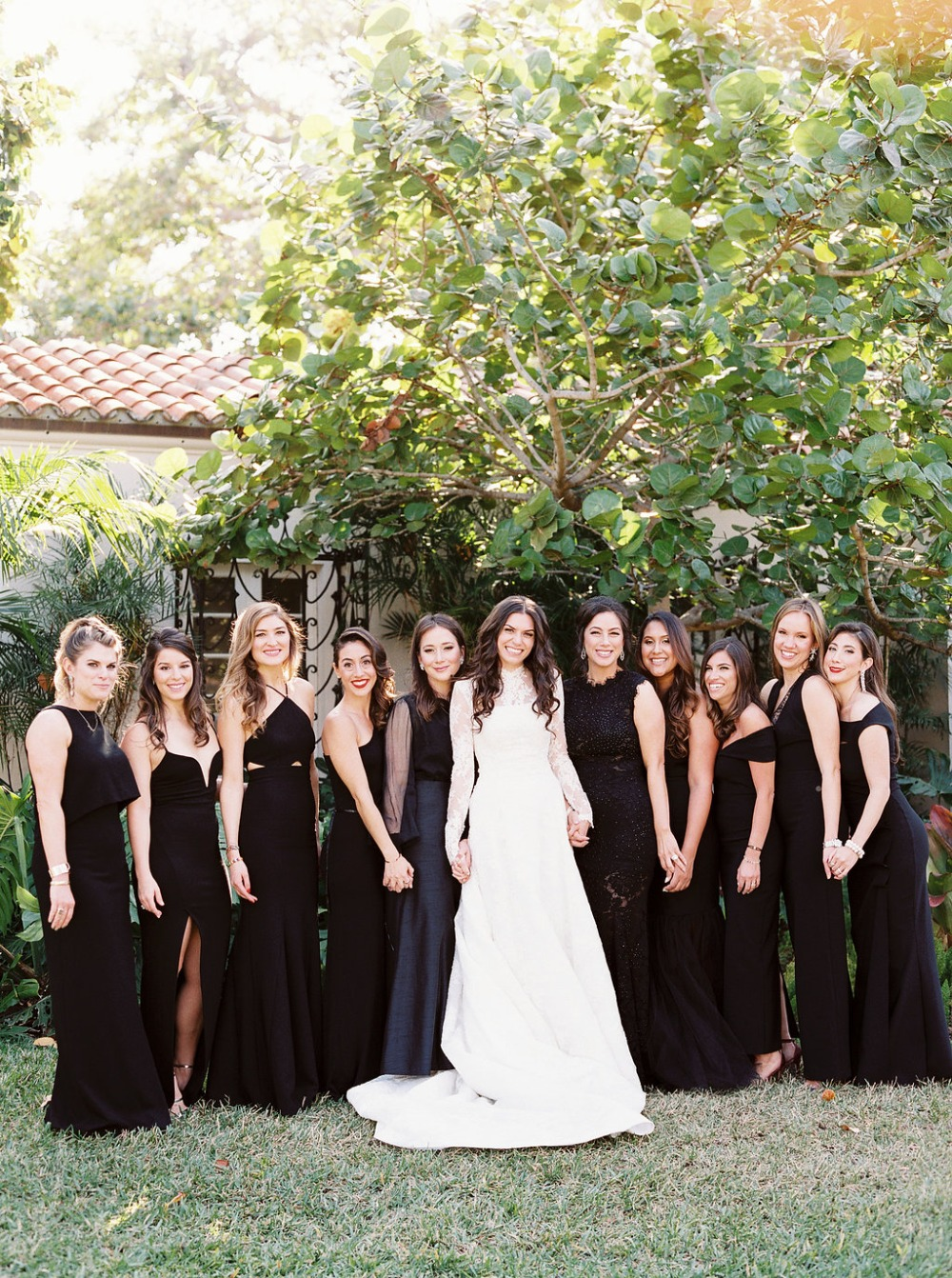 bride and all her bridesmaids in mismatched black gowns