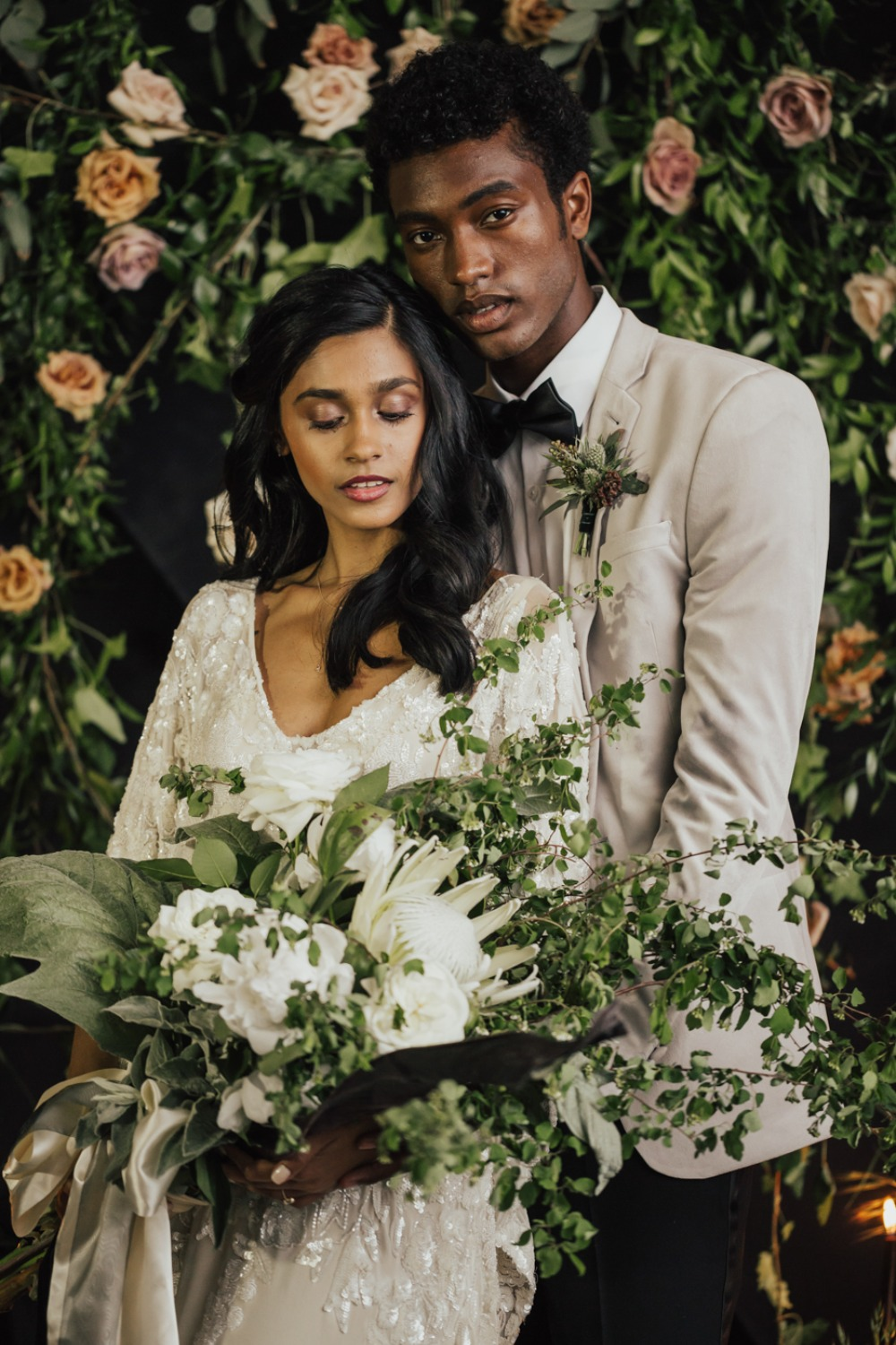 wedding couple with floral backdrop