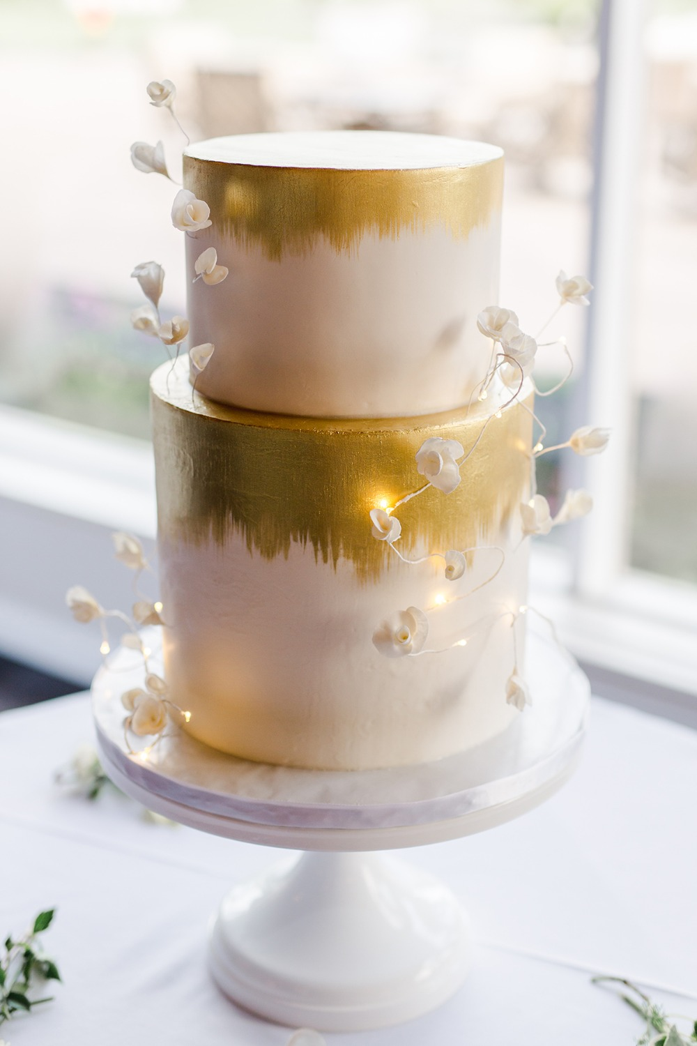 gold leaf painted cake with fairylight accents