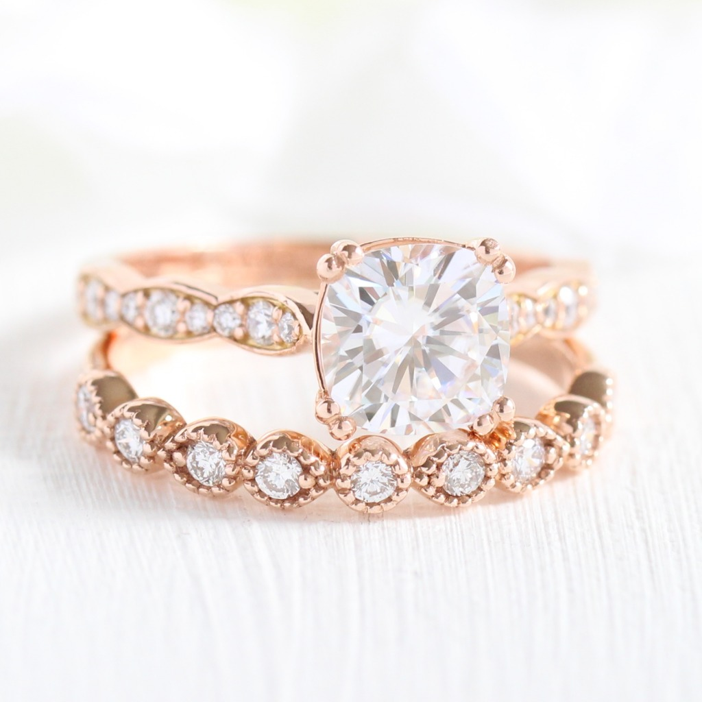 Vintage-inspired bridal set of Solitaire Cushion Moissanite in Scalloped Diamond Band paired with Milgrain Diamond Band. See more from
