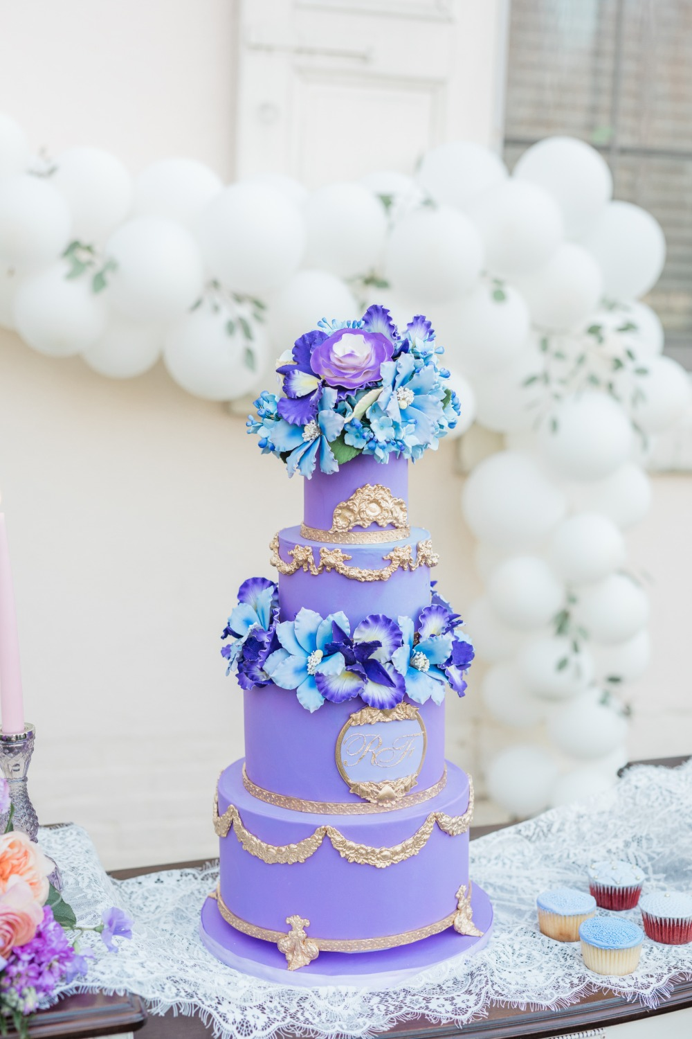 purple and gold wedding cake topped with sugar flowers