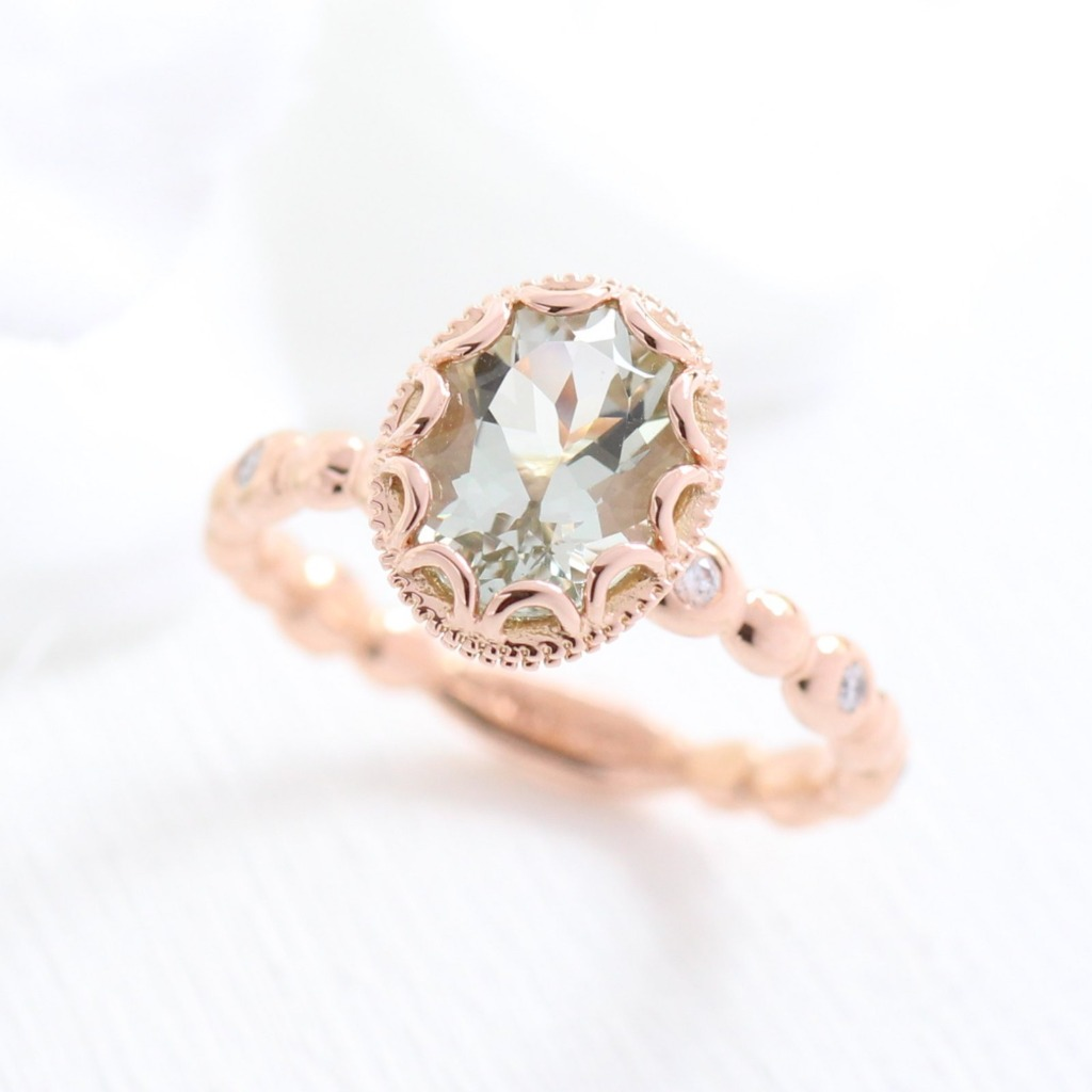 This oval green amethyst featured in this floral solitaire engagement ring in pebble diamond band sets the perfect look of vintage