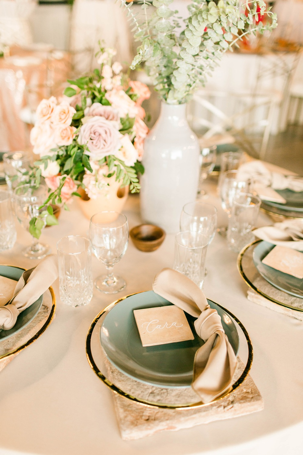 neutral and teal wedding place setting with tile chargers and place cards