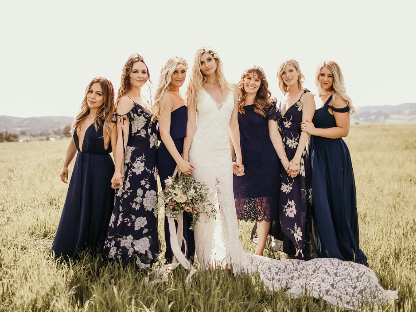 the bride and her bridesmaids in mismatched navy