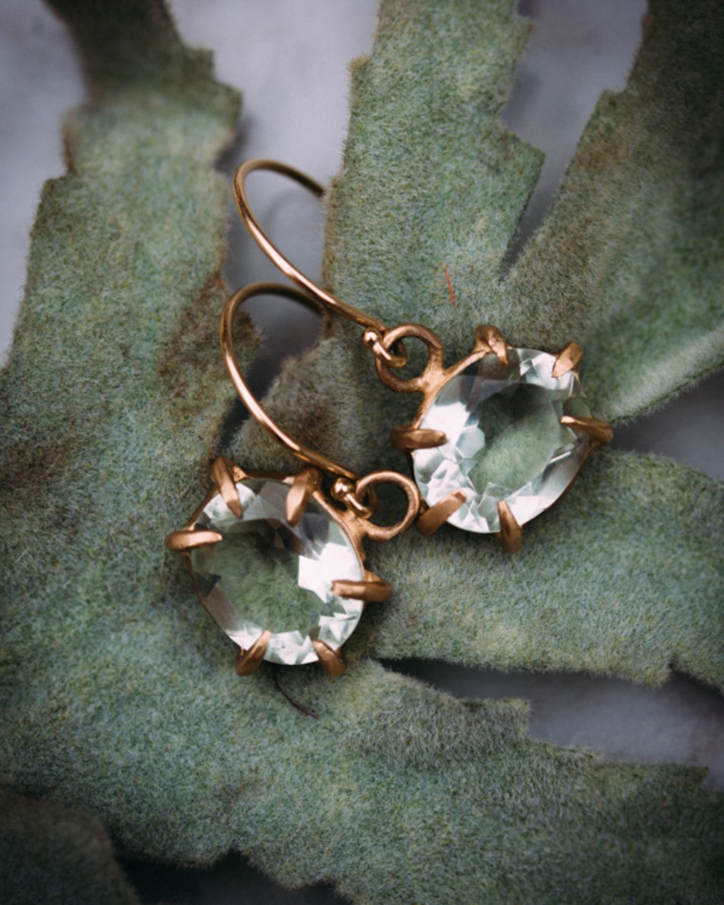 This pair of earrings feature green amethyst oval drops set in 14K yellow gold. Simplistic and edgy perfect for everyday wear!