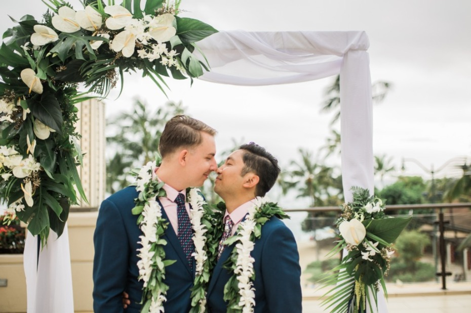 Two grooms sharing a smooch after their wedding ceremony
