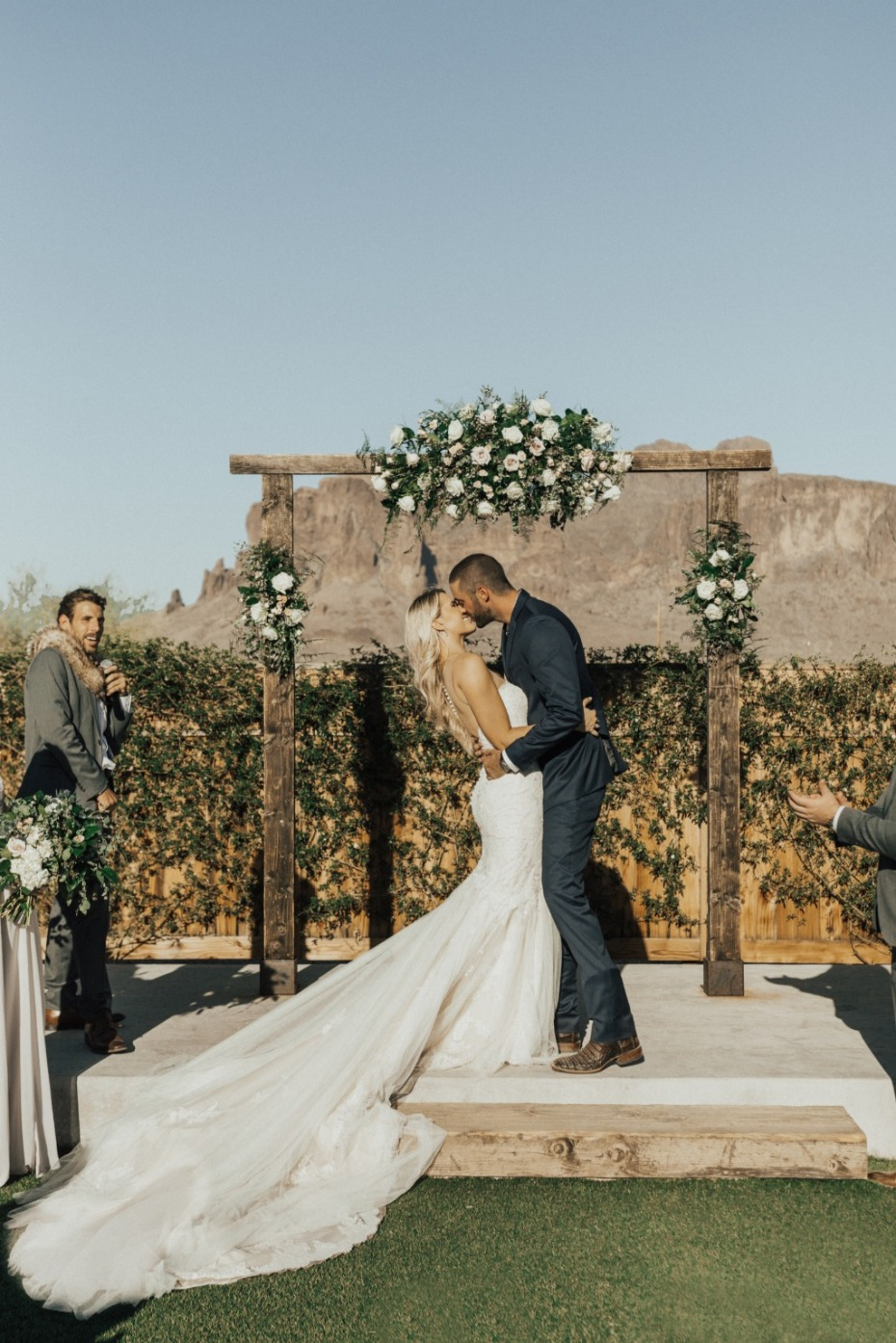 Bride and groom's first kiss at altar with mountain in back