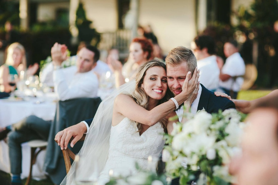 Bride and groom embracing during wedding speech