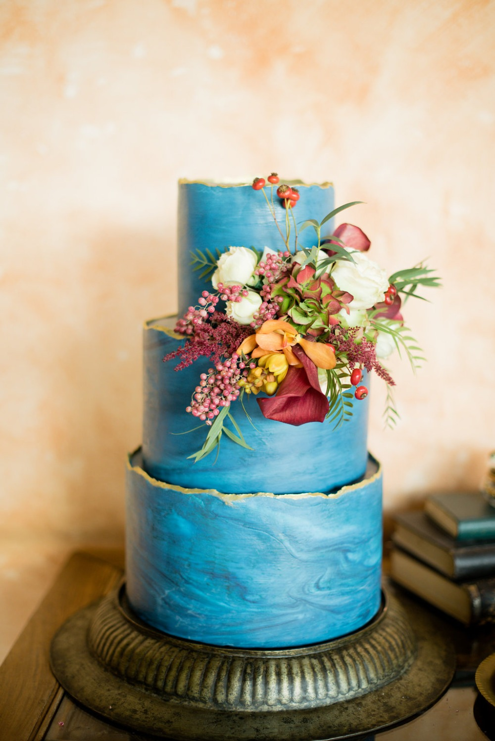 Marbled blue and gold cake with floral accent