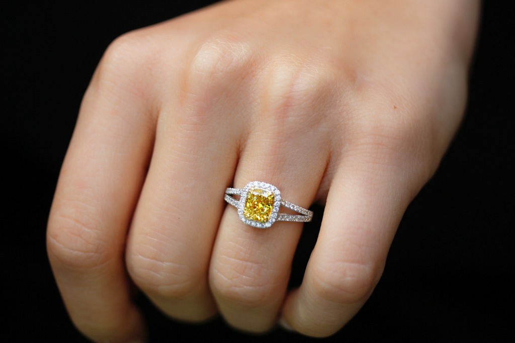 A fancy vivid yellow diamond is cushion cut and set on the center of this astoundingly regal design. Encircled by a loop of white diamonds