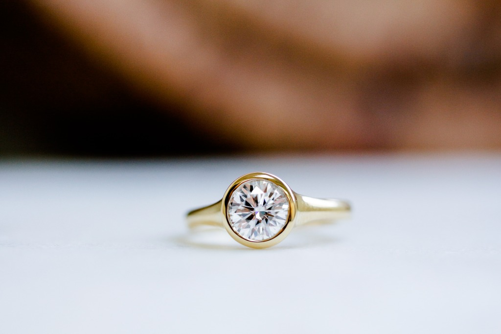 A one carat round brilliant-cut diamond is bezel set on this classic solitaire style engagement ring. We really love the modern look