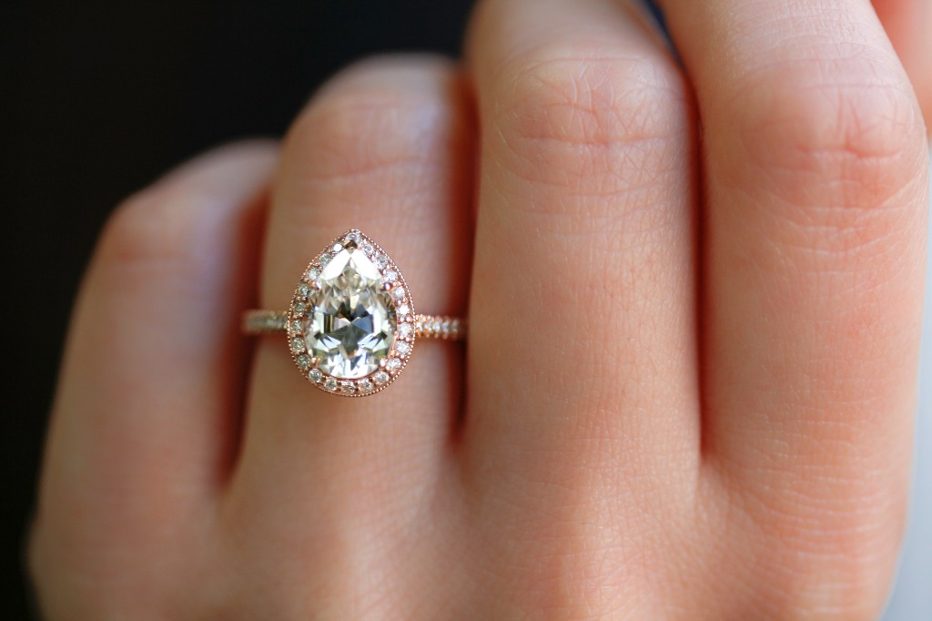 This stunning engagement ring features a 2 carat pear-shape moissanite gemstone and round-cut side diamonds set in solid 14-karat rose