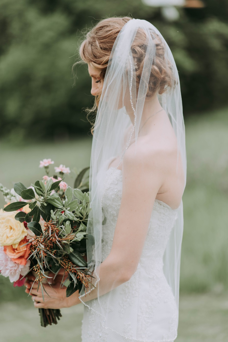 Bride looking down at her bouquet with veil on