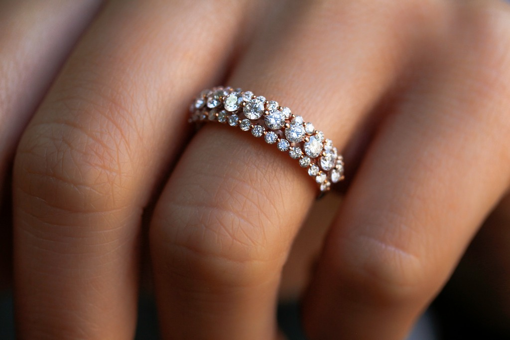 Three sets of real diamonds are sectioned into adjacent rows along this fashionable ring. With two smaller rows surrounding a bigger