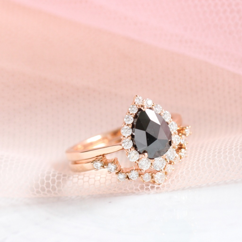Unique pear shaped rose cut black diamond ring in rose gold halo diamond ring setting nesting perfectly with a curved diamond wedding