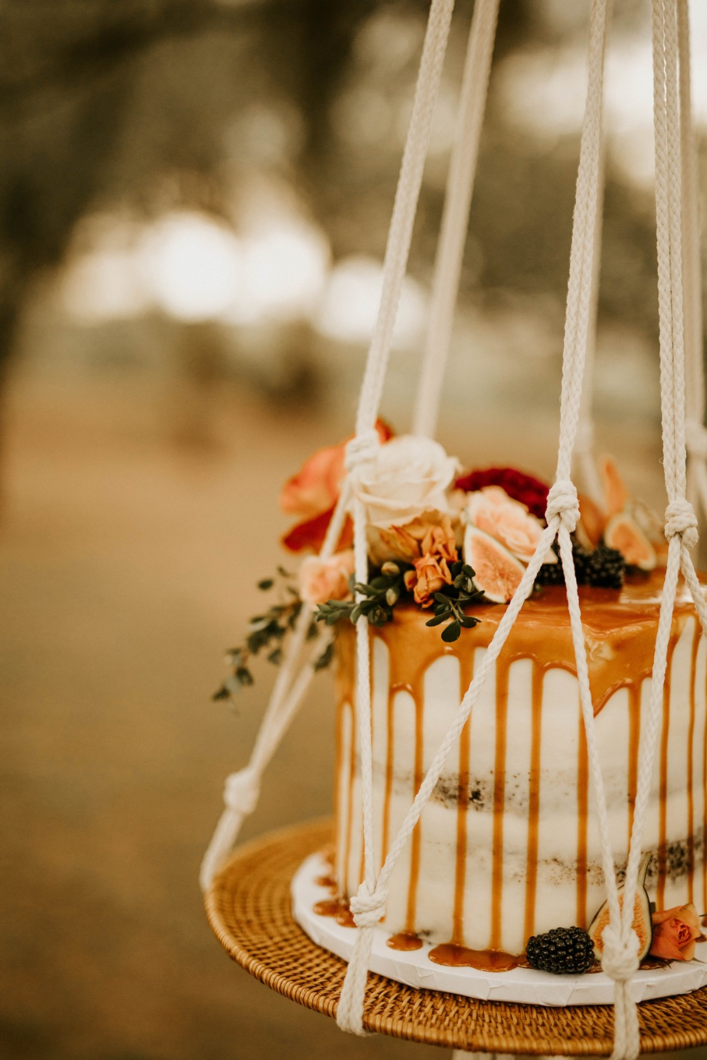 flower topped drizzle cake in a macrame swing