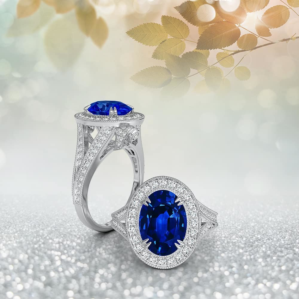 The GIA certified oval sapphire is double-claw set in luminous metal and surrounded by a halo of glimmering diamonds. Weighing 3.48