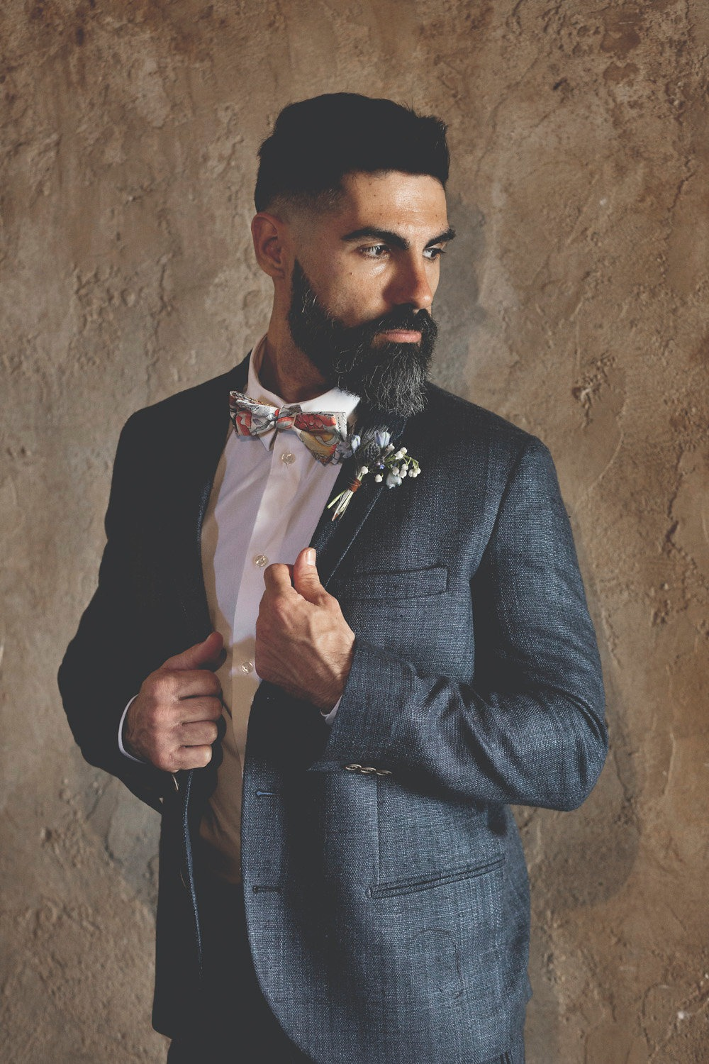 groom in navy suit and floral bow tie
