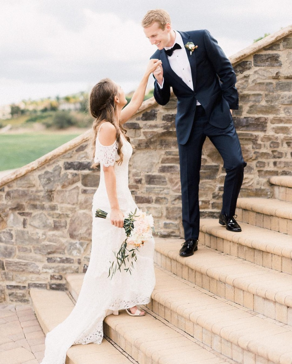 Groom kissing bride's hand while ascending stairs