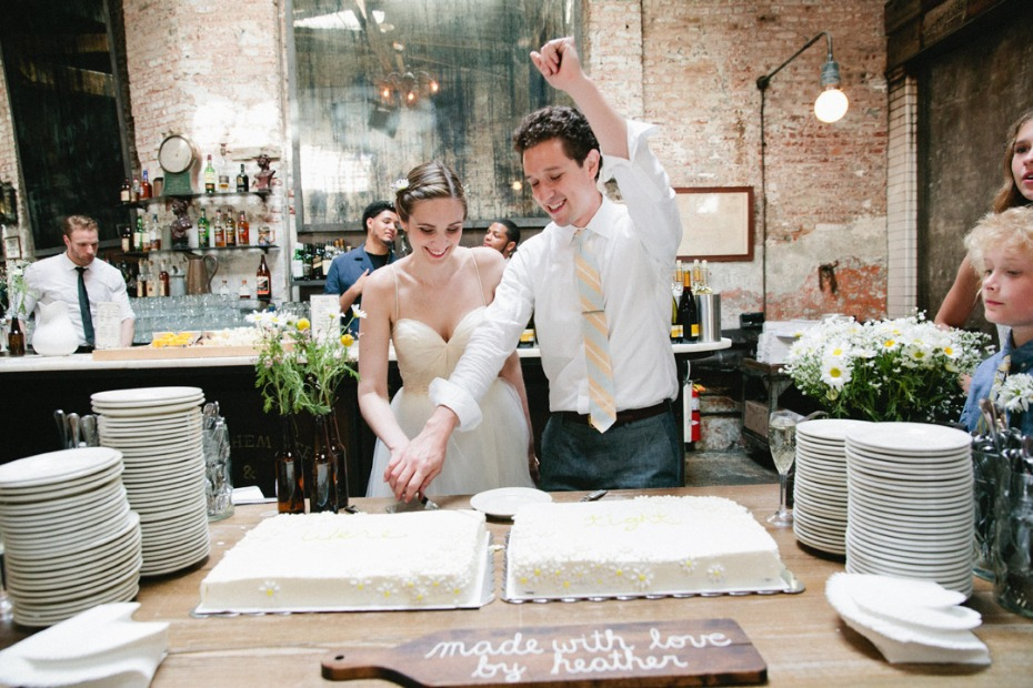 Bride and groom cutting the cake at beer hall wedding