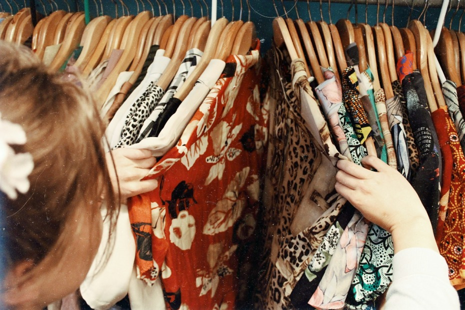 Woman looking through clothes in her closet