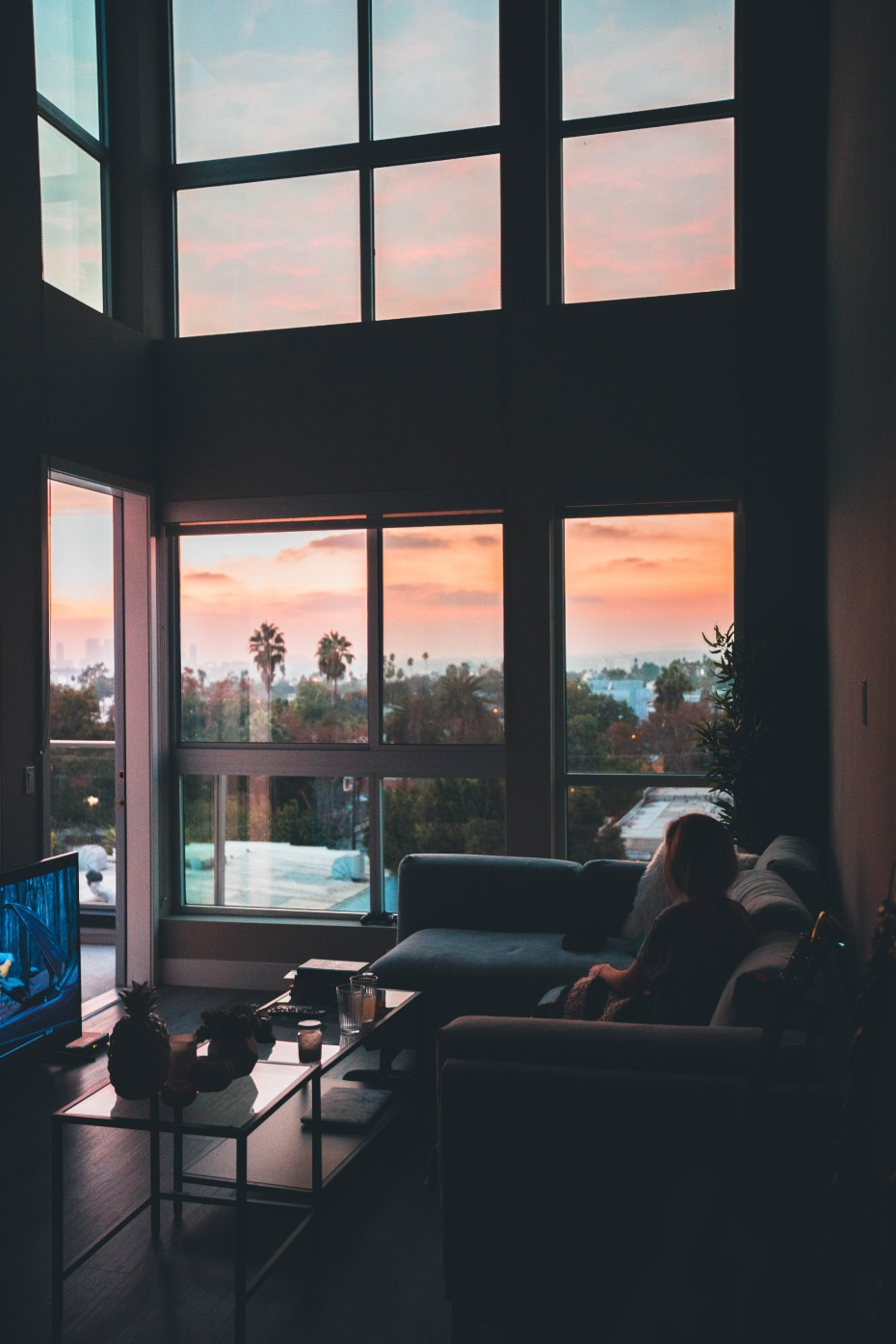 Woman watching tv with sun setting outside
