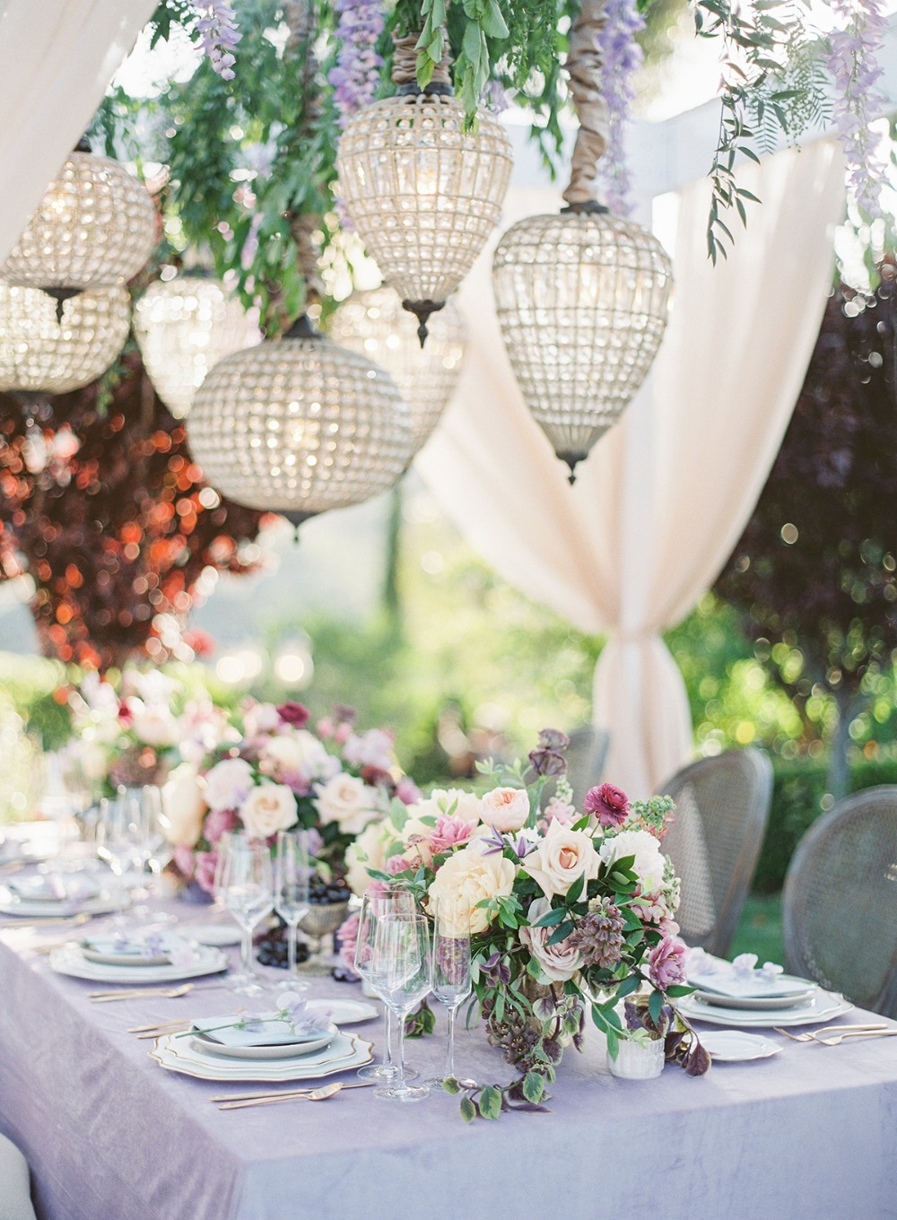 glamorous garden party table with floral and chandelier canopy