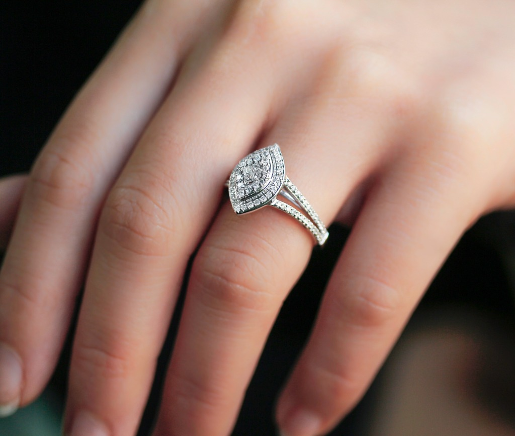 A series of many small diamonds are joined together over a tiered double halo boat shaped setting. Four princess-cut diamonds are affixed