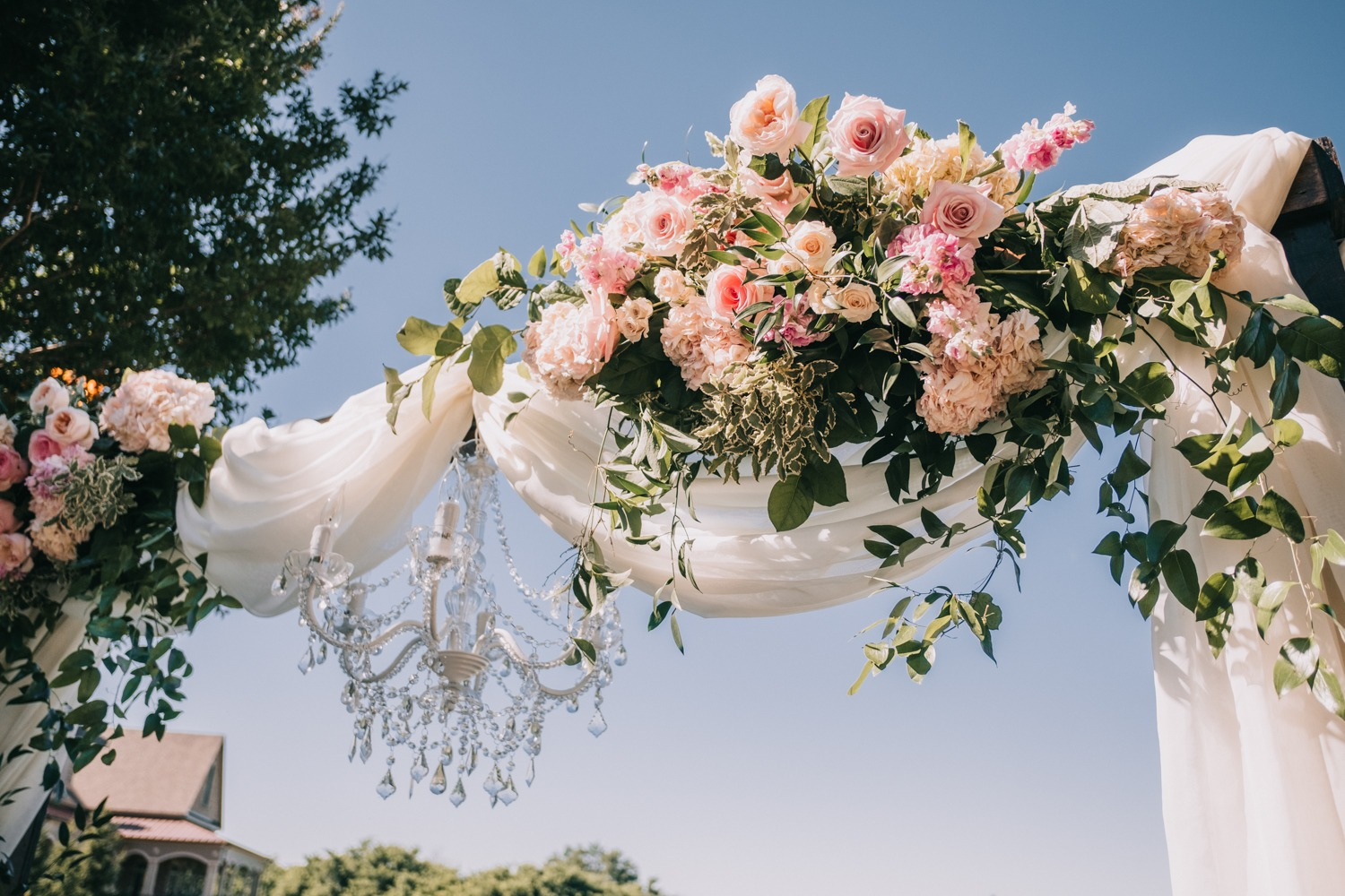 wedding chandelier and flower accented arch