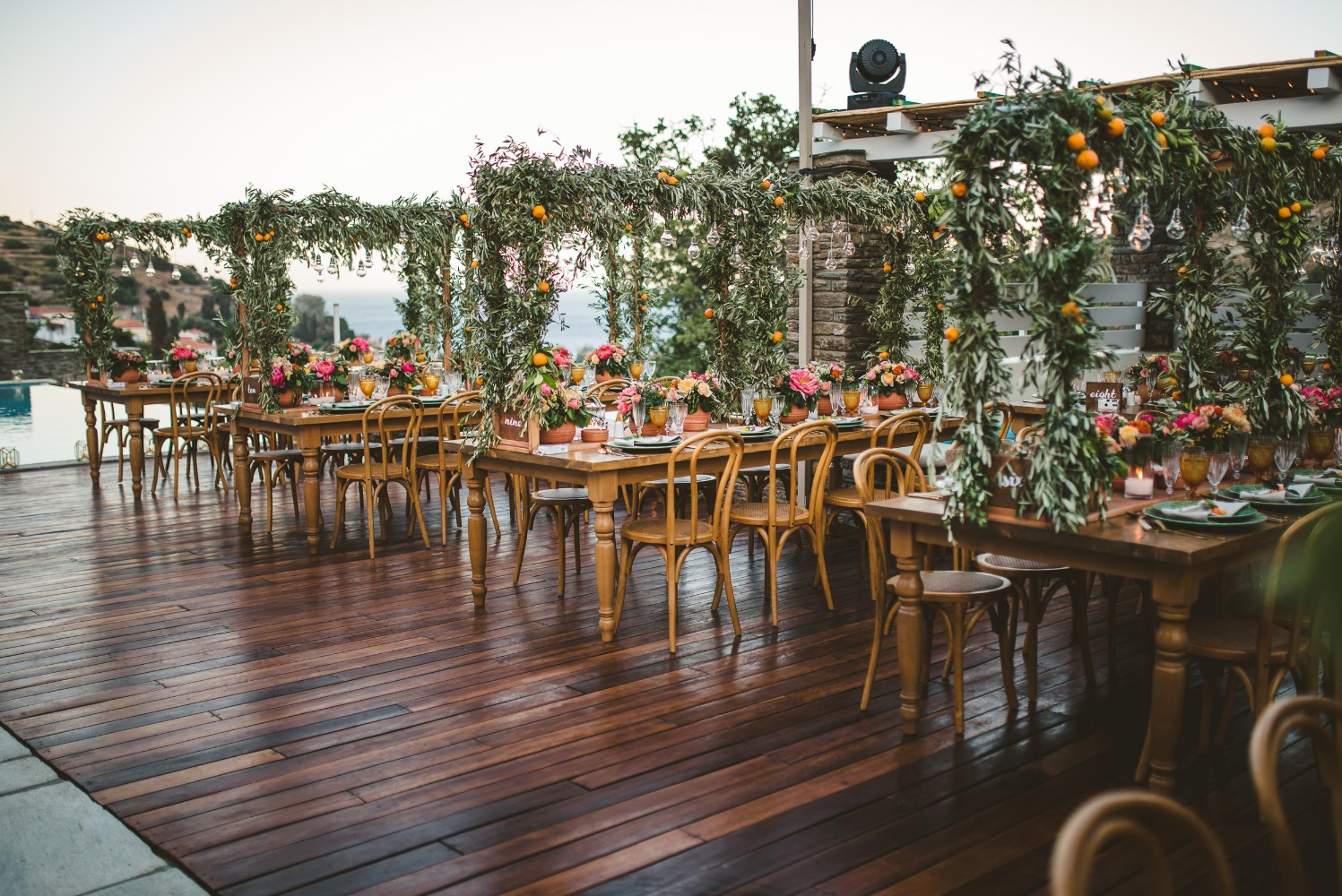 outdoor wedding tables with floral covered pergolas over them