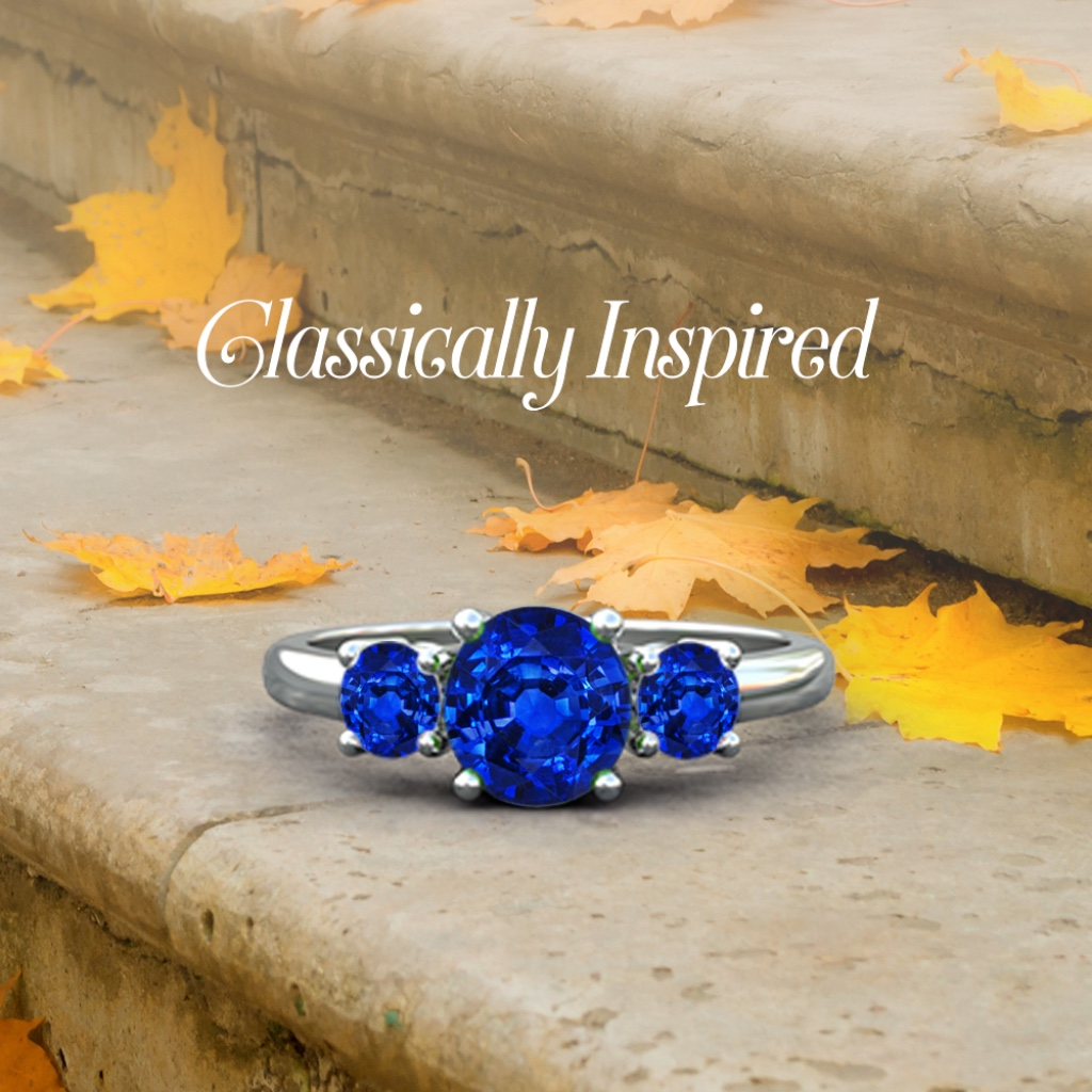 This 14k white gold three stone blue sapphire ring captivates the senses with its alluring brilliance. The prong settings of the round