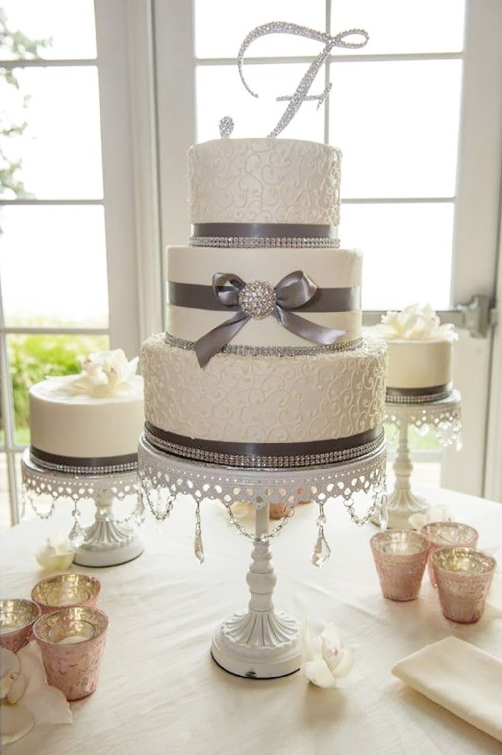 Shades of grey ribbon with sparkle on white tiered wedding cake. Opulent Treasures white cake stands with chandelier accents. Opulent