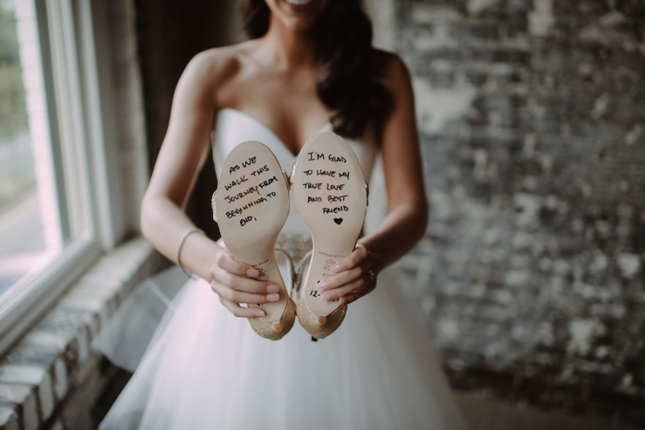 Bride holding shoes with message from husband
