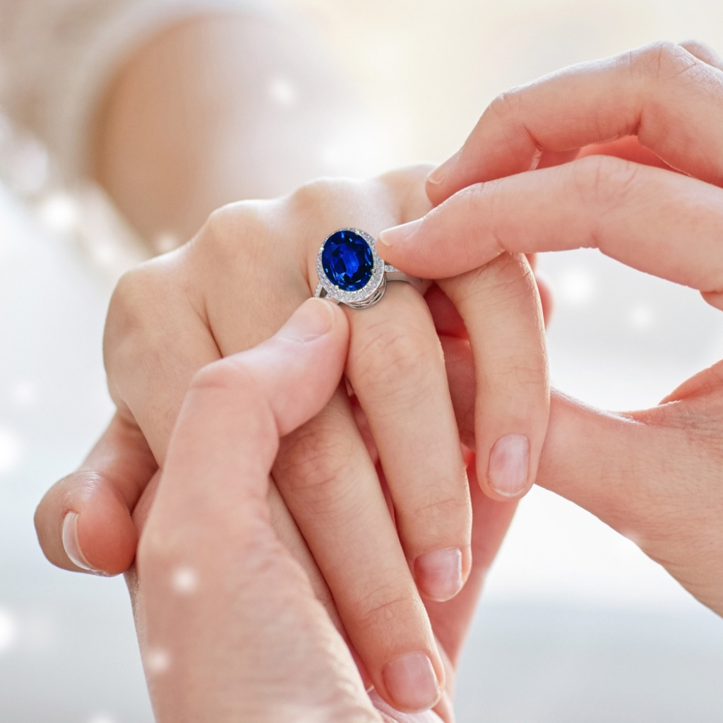 The prong set blue sapphire sits beautifully within a glimmering halo of diamonds. Additional diamond accents on the split shank and