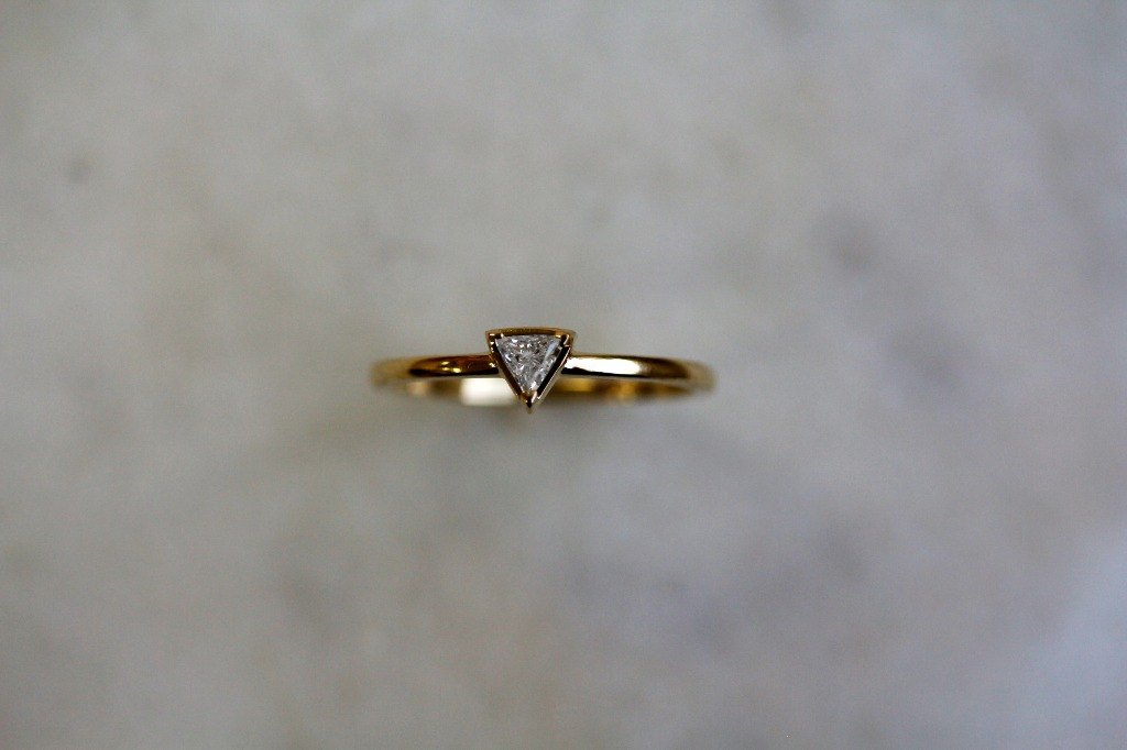 This slender diamond ring carries a triangular accent-sized diamond on solid 14-karat yellow gold. The dainty style is suitable as