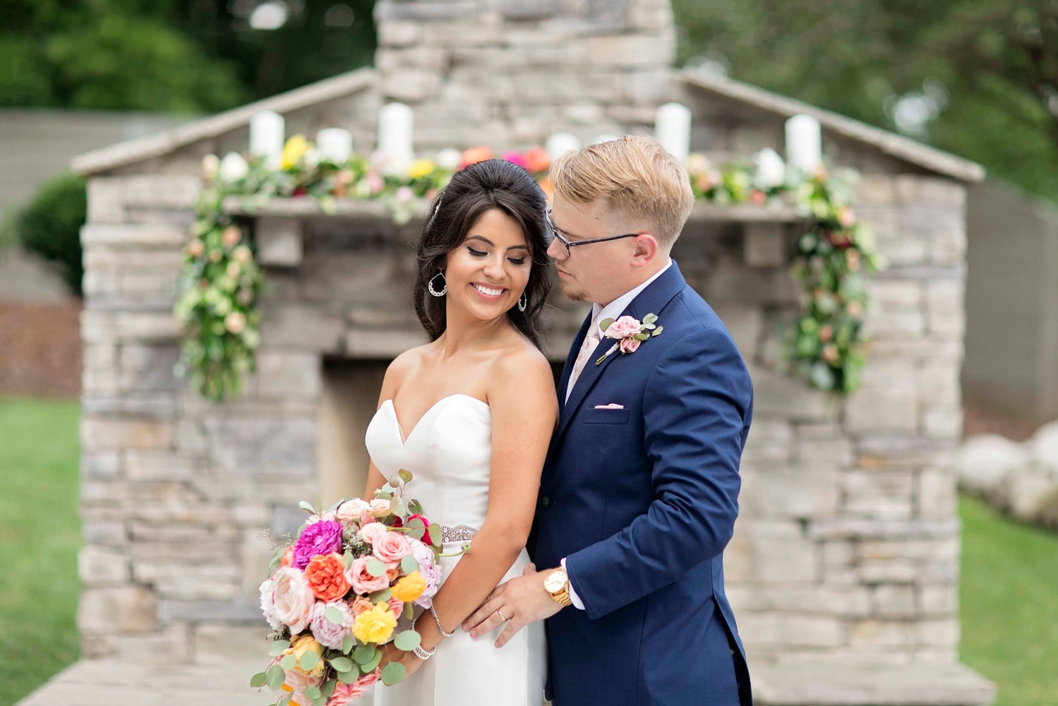 wedding couple with outdoor fireplace ceremony backdrop