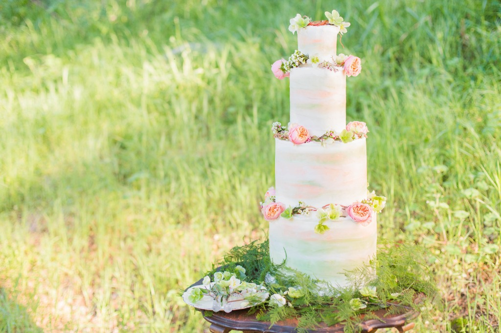 Soft, nature colors in a perfect woodland setting. We love this simple cake dressed in florals and greenery to match the venue's style