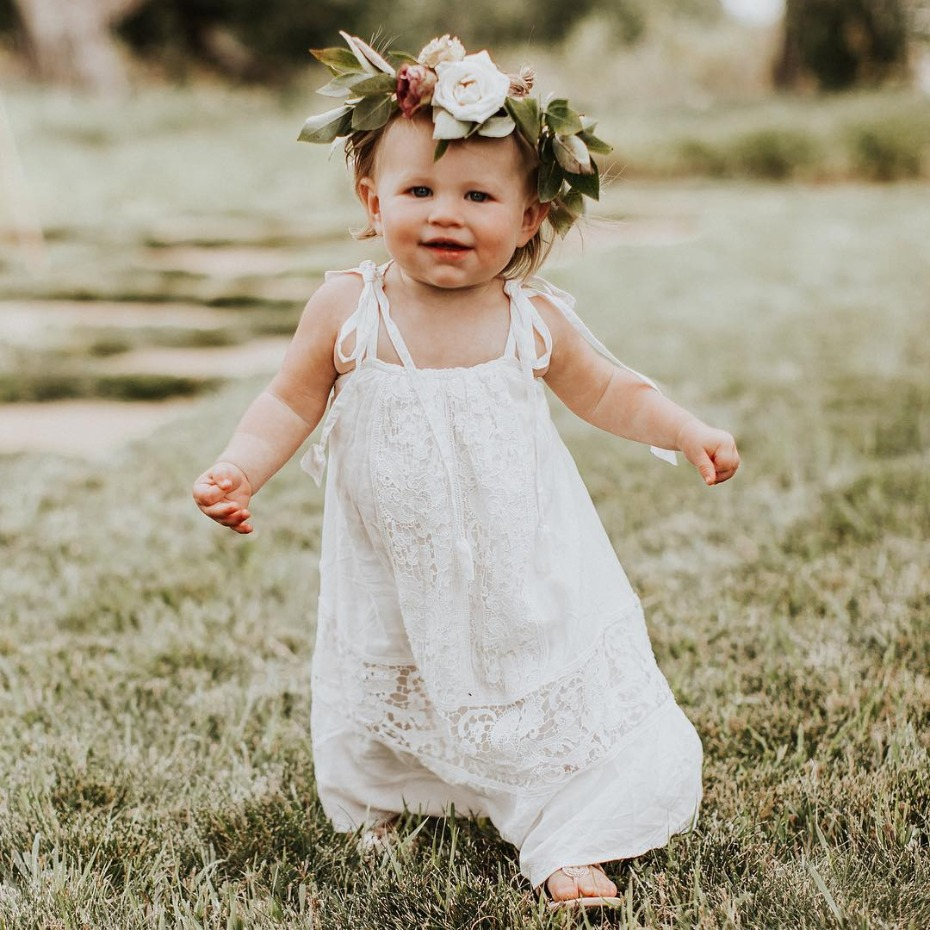 Flower girl walking in dress with flower crown