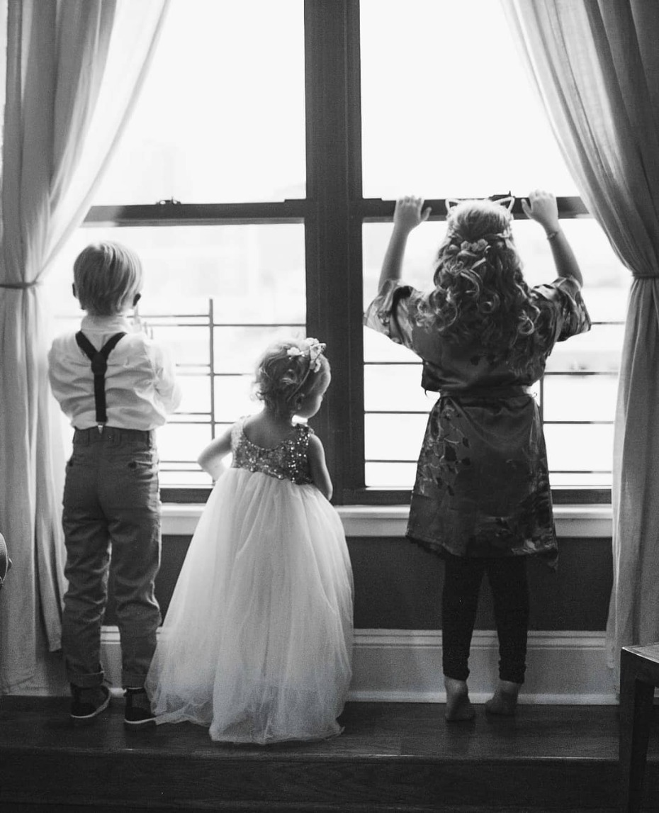 Flower girls and ring bearer staring out the window