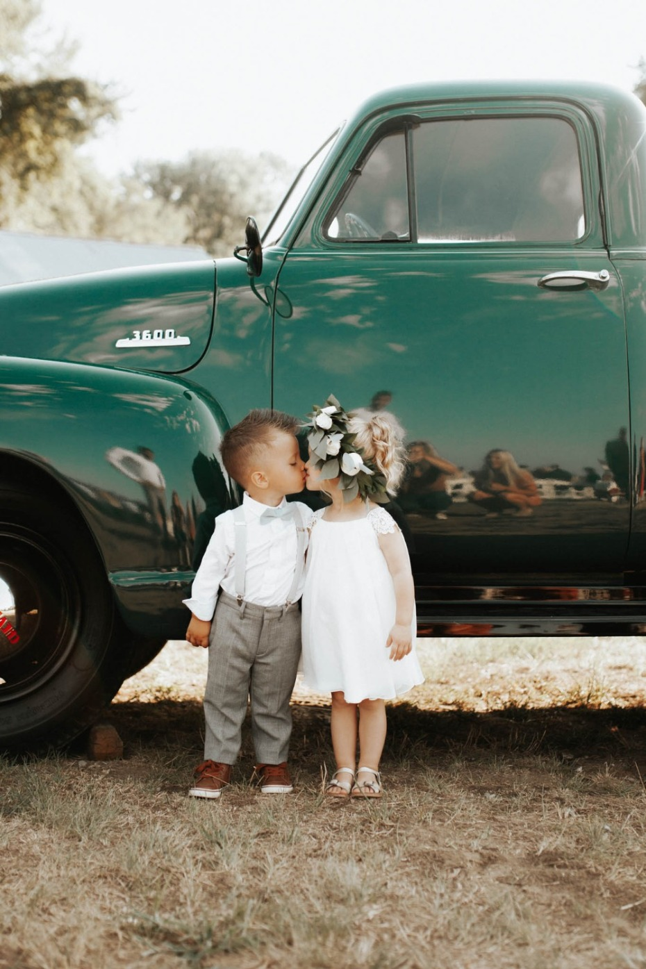 Ring bearer and flower girl kissing next to truck