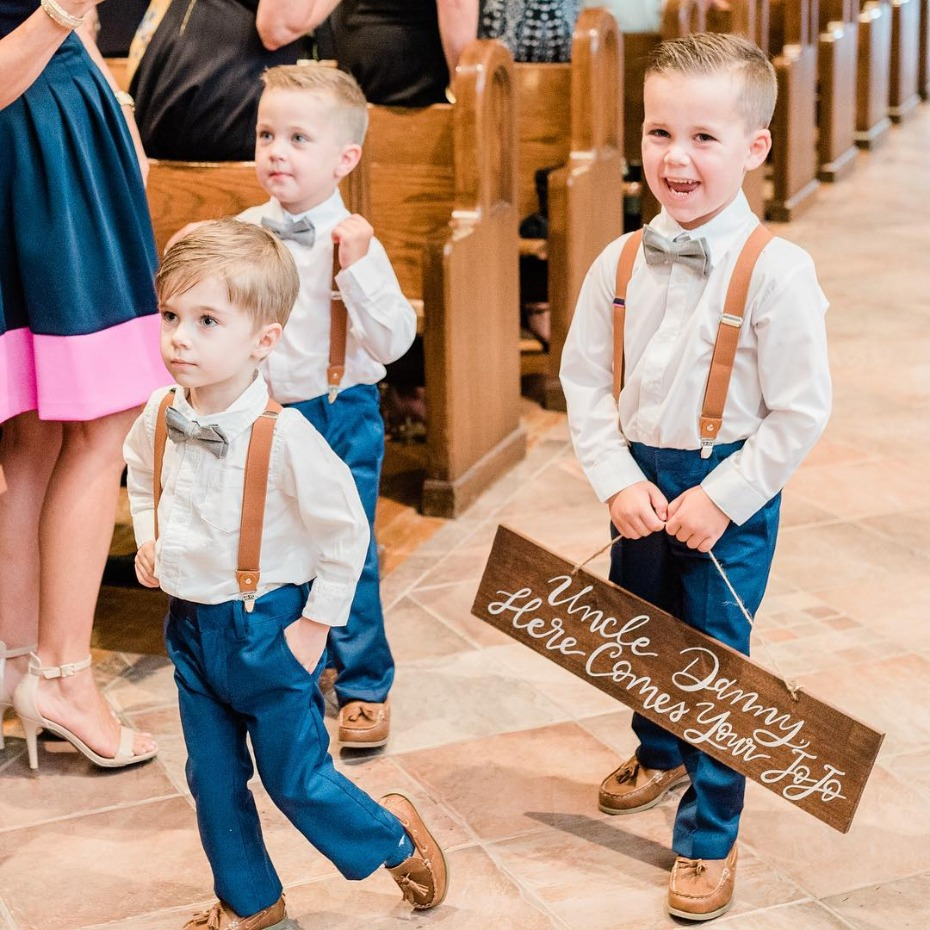 Ring bearers carrying sign down the aisle