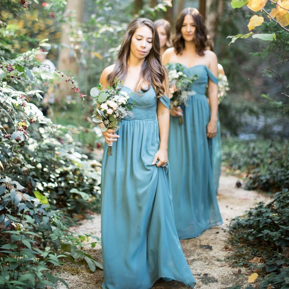 Bridesmaids walking with bouquets in the forest