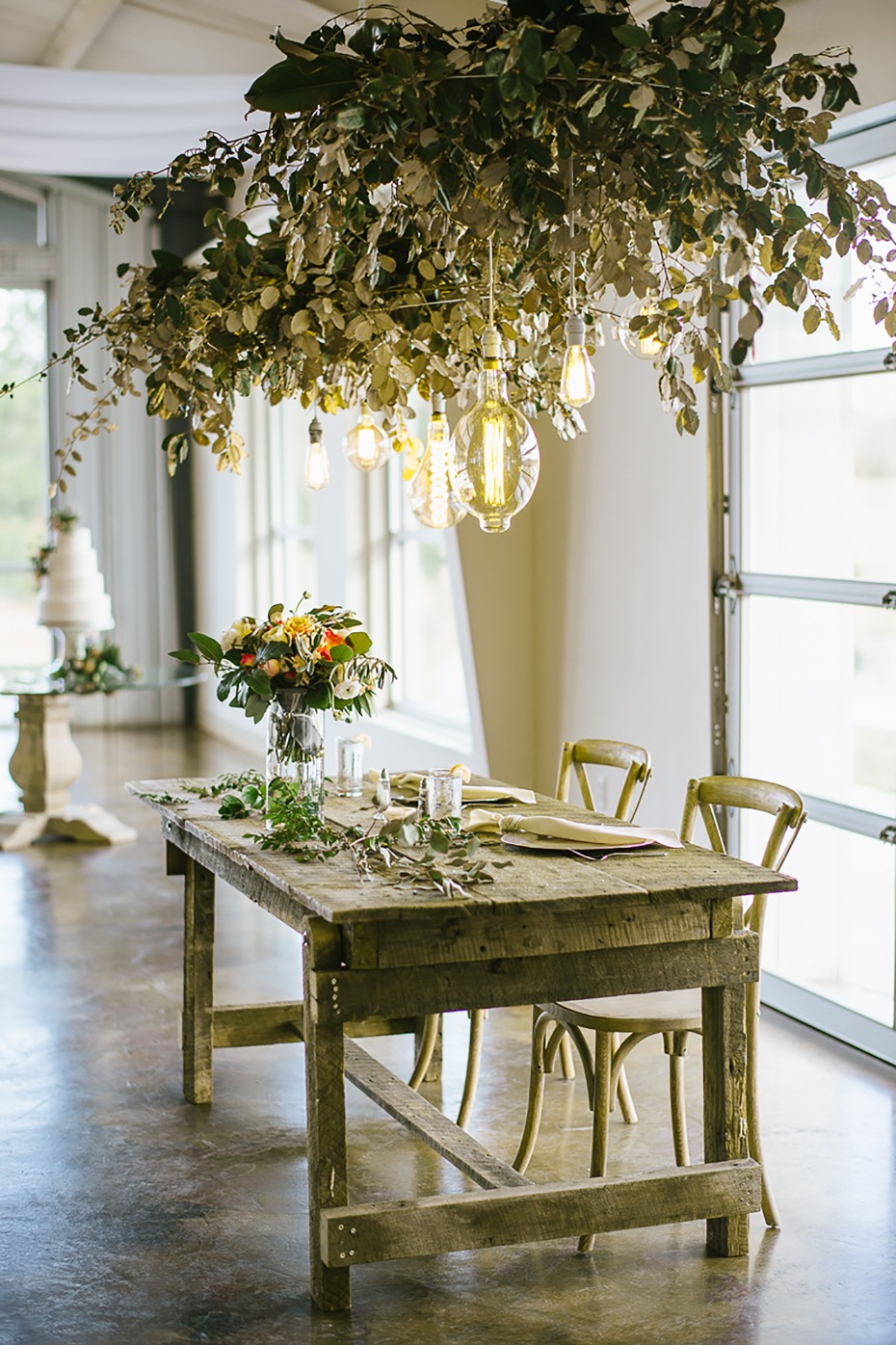 Sweetheart table with greenery and hanging bulbs