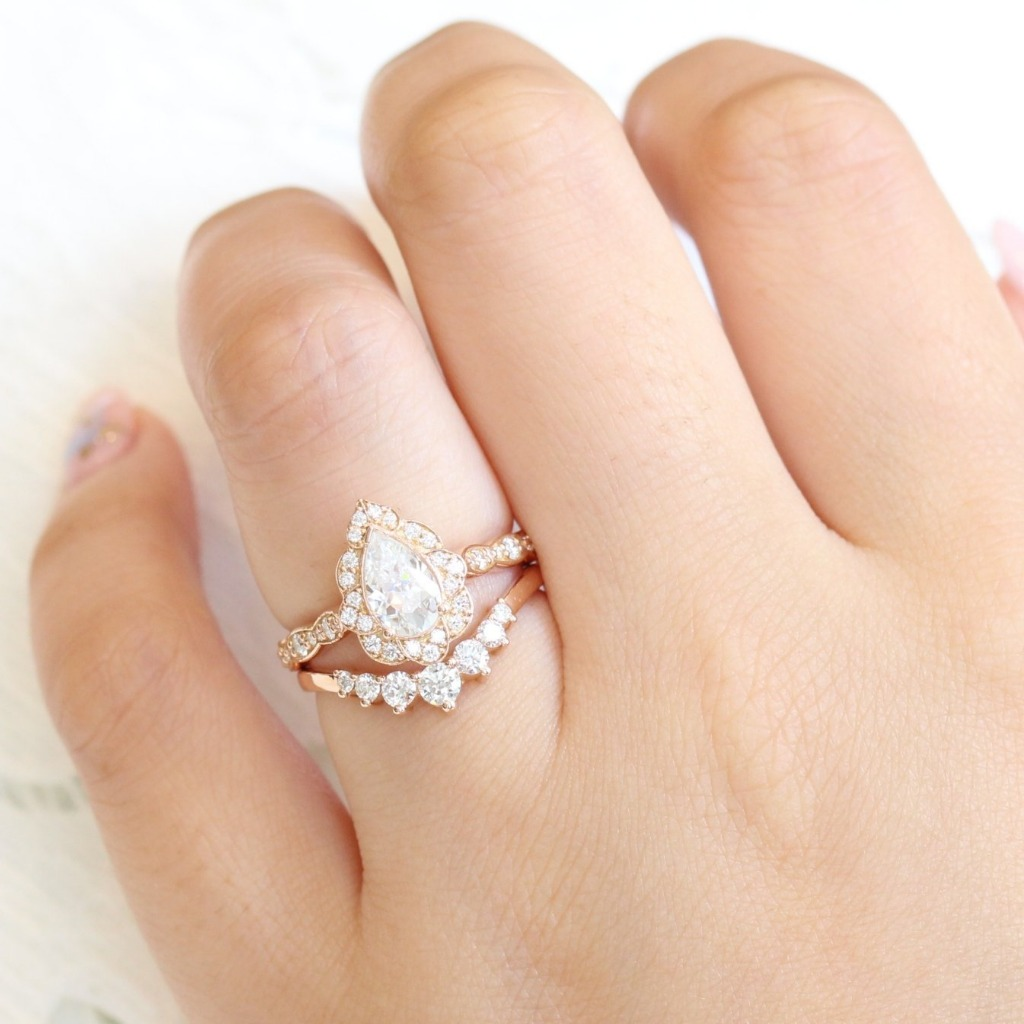 Breathtakingly one of a kind creation! This unique moissanite bridal set features a pear moissanite engagement ring in 14k rose gold