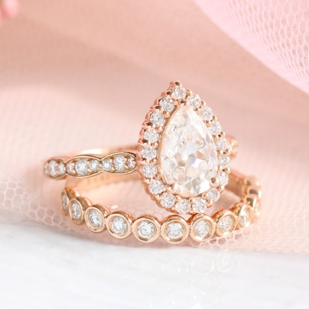 Pear moissanite diamond halo engagement ring in rose gold pairs perfectly with bezel diamond wedding band as a lovely bridal set by