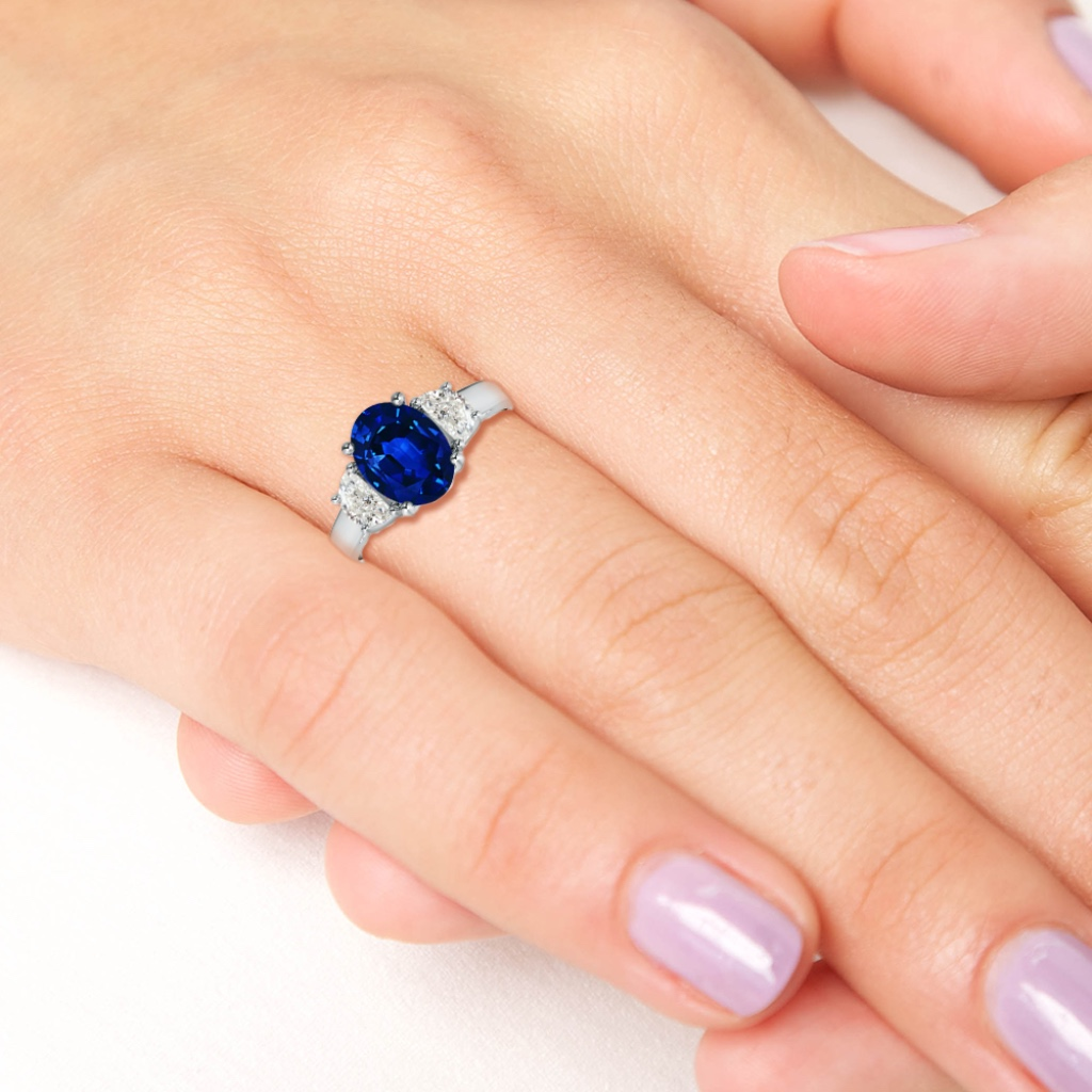 The oval blue sapphire is prong set amid two sparkling half moon diamonds to form a remarkable three stone combination. A beautiful
