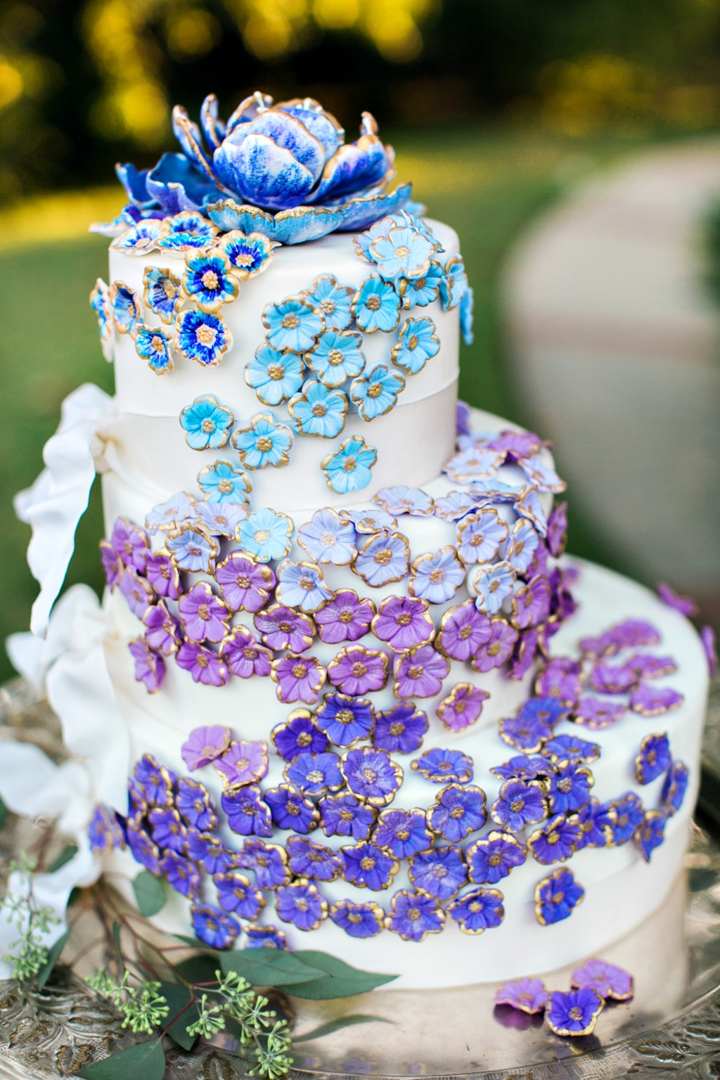 For the couples looking to add some color and uniqueness to their wedding cake, this whimsical three-tier cake has ombré blue to purple