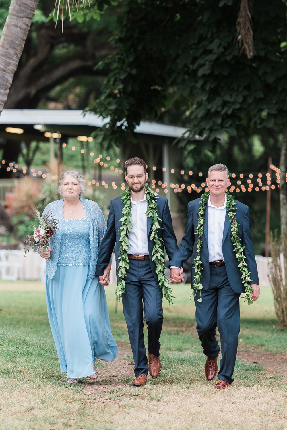 groom being walked down the aisle by mother and father