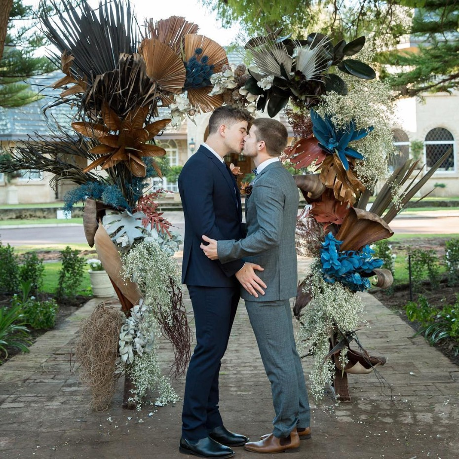 Grooms embracing in front of ceremony arch - @theflowergirlperth